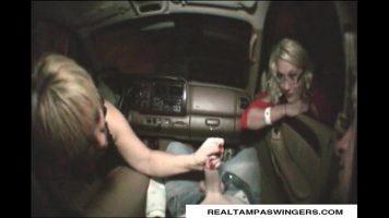 Un barbat care sta relaxat pe spate in masina si este satisfacut de doua tinere blonde